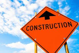 Orange sign with black words saying CONSTRUCTION