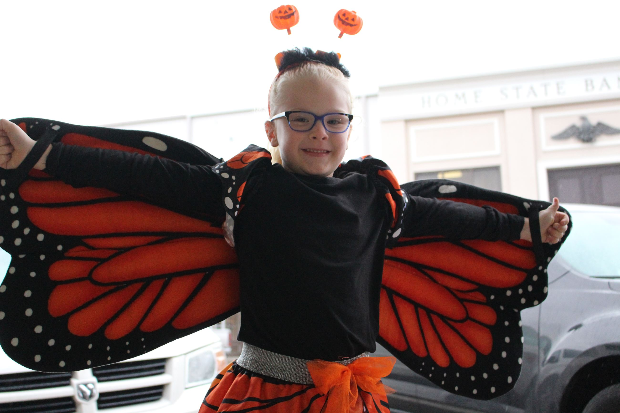 Girl in black and orange butterfly Halloween costume