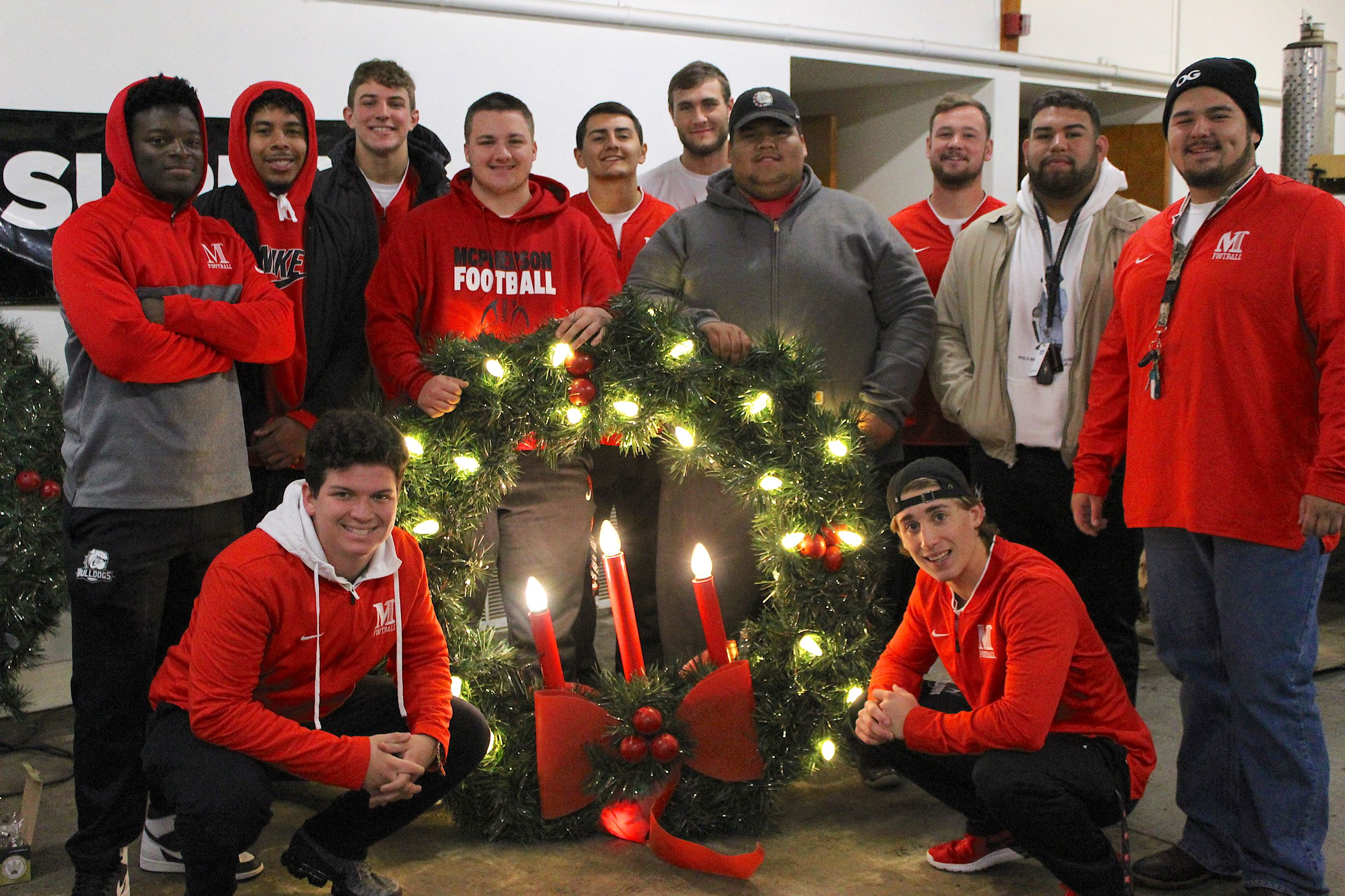 Twelve college football players surround a giant Christmas wreath