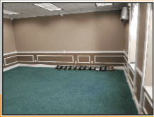 Empty office space with aqua colored carpet and tan walls