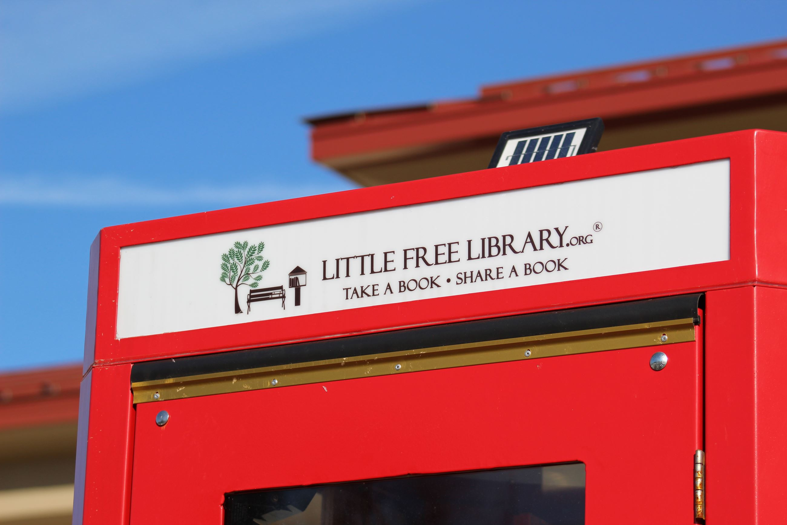 Top corner of a red phone booth with a sign advertising a LITTLE FREE LIBRARY