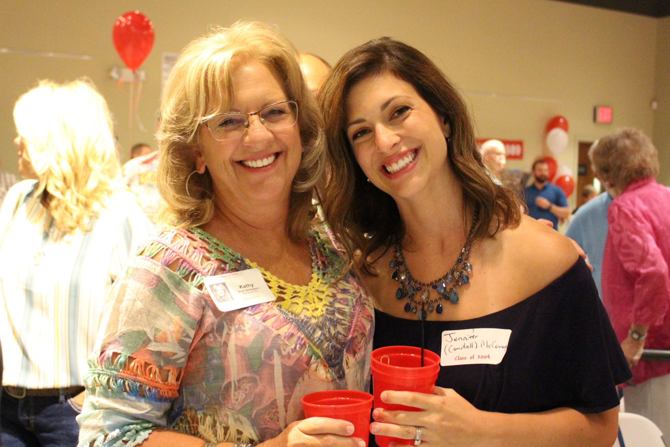 Two women celebrate together at the MHS class reunion