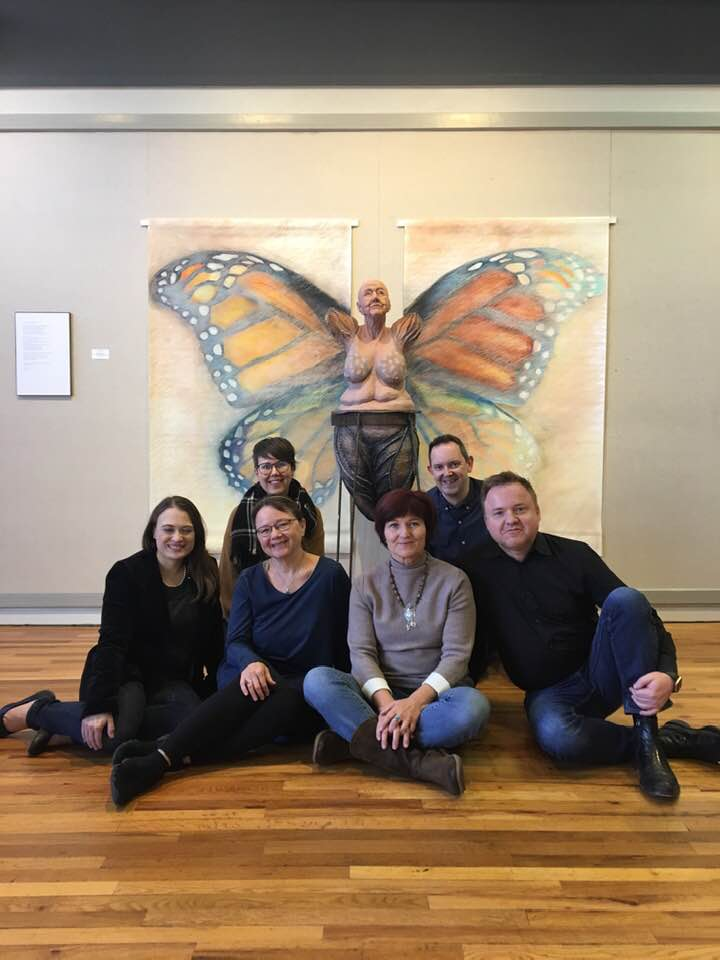Six fine arts instructors from McPherson College pose in front of artwork in Friendship Hall