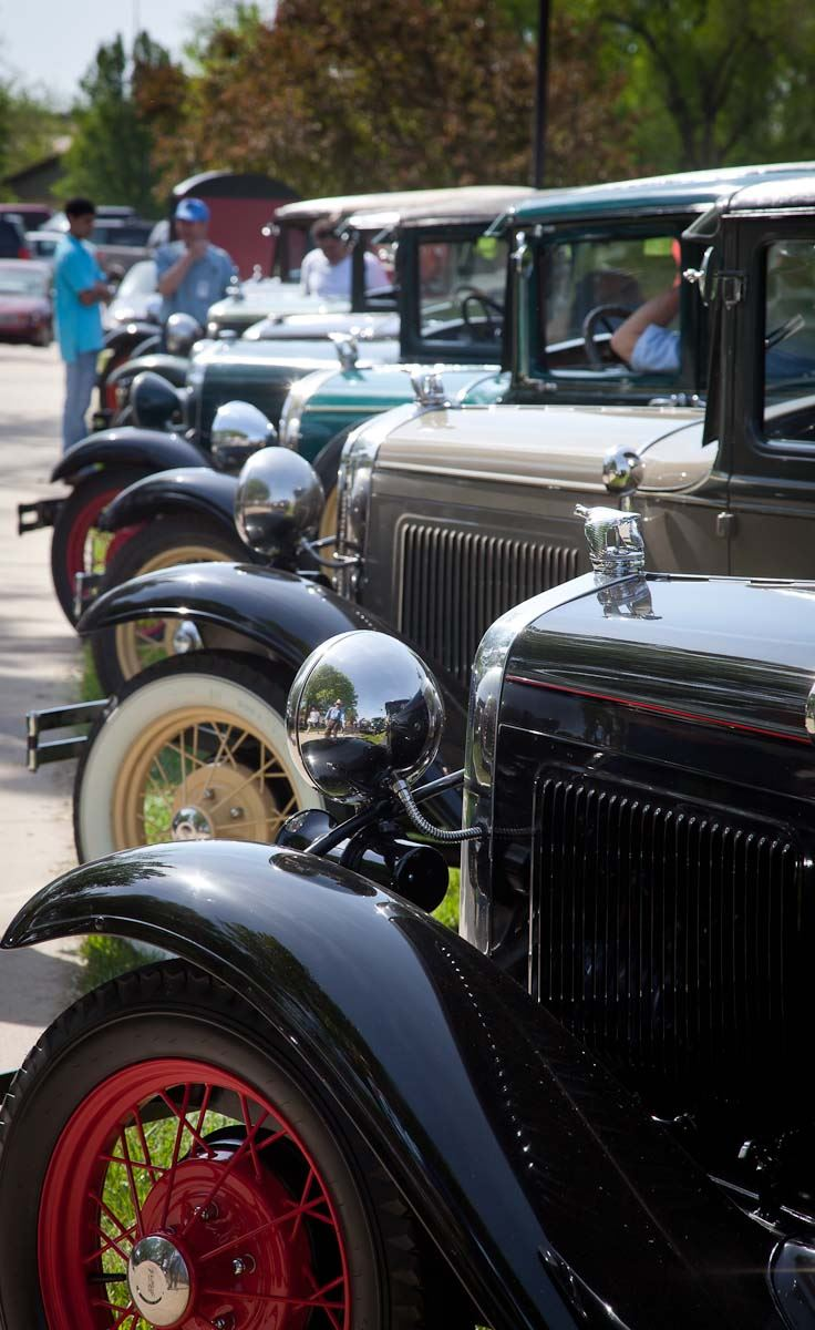 Antique automobiles lined up on the street.