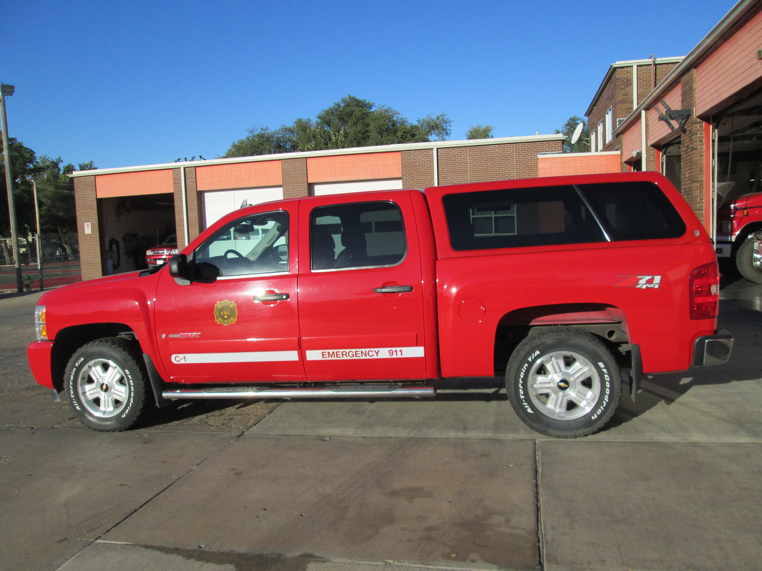 Red and white sports utility vehicle with Fire Department logo on the side.